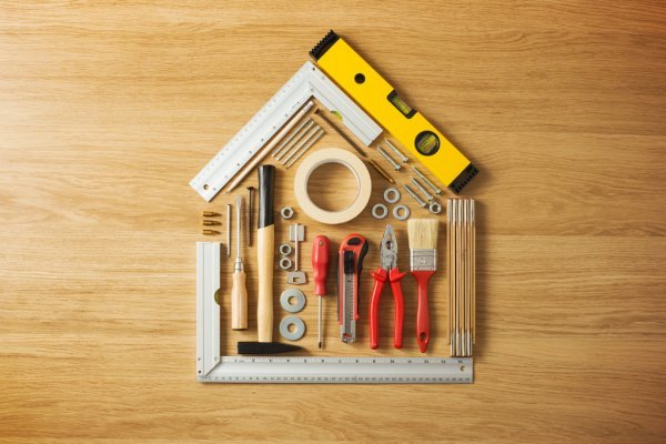 Various tools (ruler, masking tape, paintbrush, pliers, etc.) arranged into the shape of a house