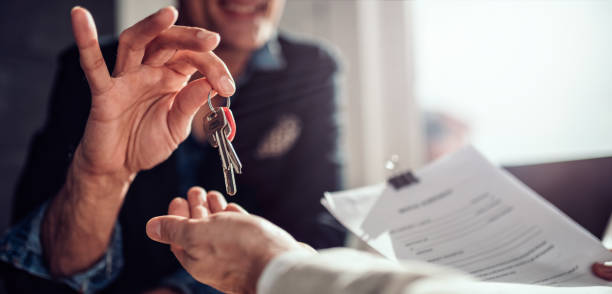 Handoff of a set of keys between two people, one person is holding lease documents.